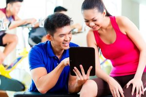 asian-personal-trainer-with-woman-in-fitness-gym